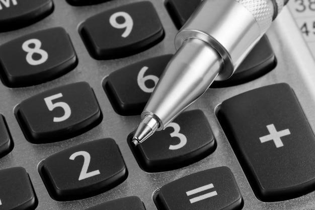 Kalkulator i długopis na tle biznesowym