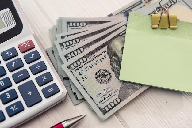 Kalkulator i długopis z pustą naklejką na banknotach dolarowych. koncepcja oszczędzania pieniędzy