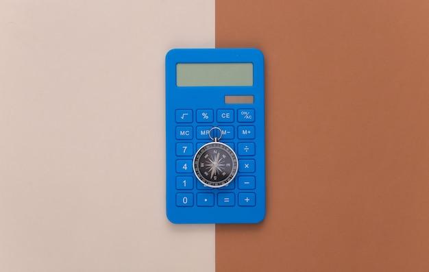 Kalkulator i kompas na beżowym brązowym tle. pomysł na biznes. widok z góry
