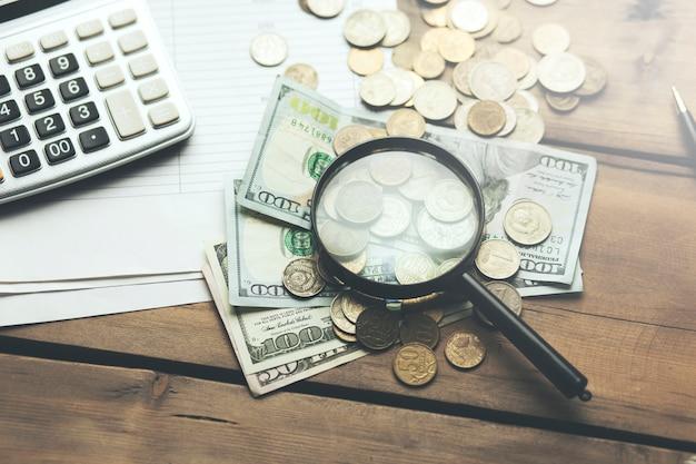 Kalkulator i lupa na książeczce bankowej z banknotem dolara