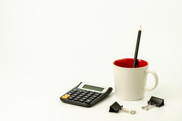 Kalkulator i materiały biurowe na białym stole.