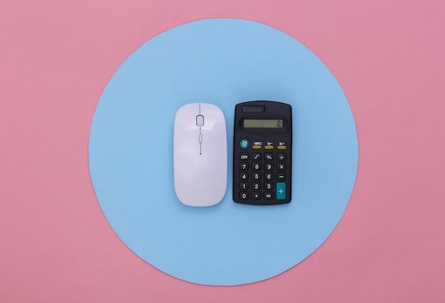 Kalkulator i mysz na różowym tle z niebieskim kółkiem. koncepcyjne studio strzał. minimalizm. widok z góry