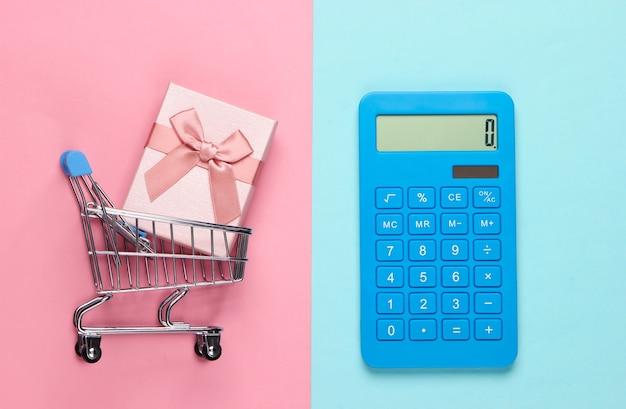 Kalkulator i wózek na zakupy z pudełkiem na różowo-niebieskim pastelu. obliczenie wartości prezentu.