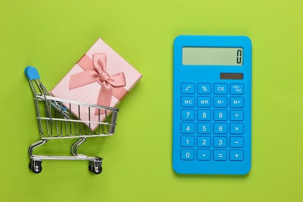 Kalkulator i wózek na zakupy z pudełkiem na zielono. obliczenie wartości prezentu.
