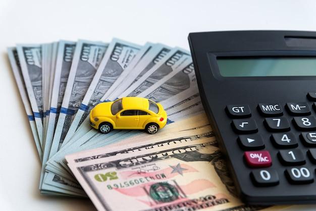 Kalkulator i żółty samochodzik na tle banknotów stu dolarowych. pojęcie kosztów zakupu, wynajmu i utrzymania samochodu
