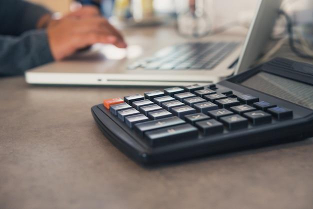 Kalkulator jest umieszczony na stole biurowym z laptopem, a zespół pracuje za kulisami.