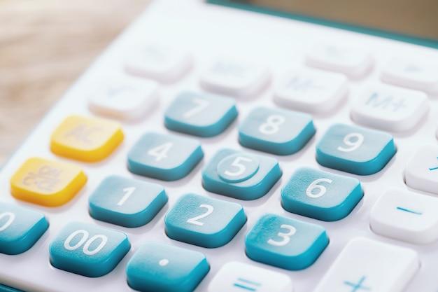 Kalkulator koncentruje się na klawiaturze z przyciskiem. kalkulator kolory niebieski żółty i biały na drewnianym stole. koncepcja obliczyć finanse konta