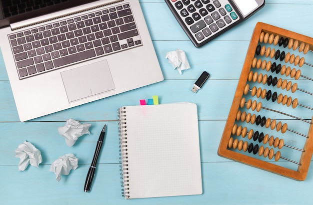 Kalkulator, laptop i stary liczydło leżą na niebieskim drewnianym stole. zmięte arkusze mówią o skomplikowanych obliczeniach. związek między pokoleniami. makieta.
