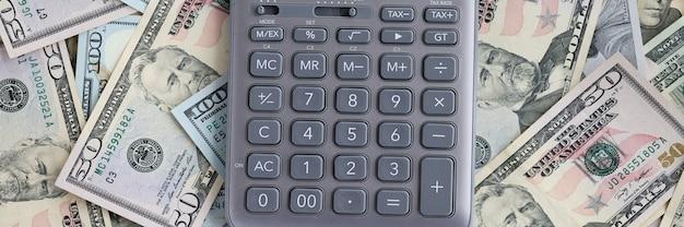 Kalkulator leżącego na zestaw zbliżenie banknotów dolar amerykański. planowanie koncepcji przychodów i wydatków