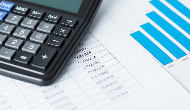 Kalkulator na białym papierze z liczbami i wykresami