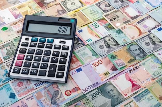 Kalkulator na tle mieszanych banknotów, z bliska