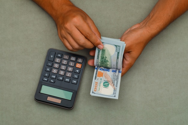 Kalkulator na zielony szary stół i człowiek liczenia banknotów dolarowych.