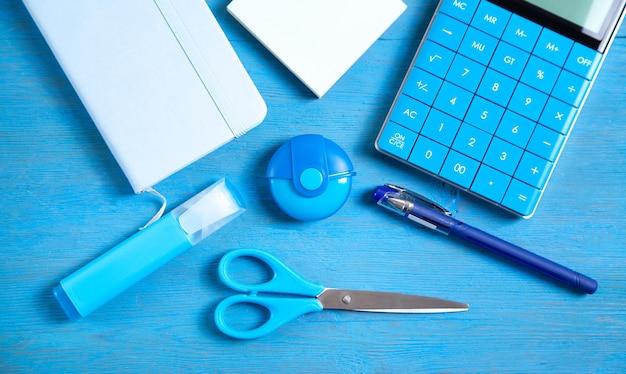 Kalkulator, notatka, gumka nożyczki, długopis, marker, karteczki na niebieskiej powierzchni.