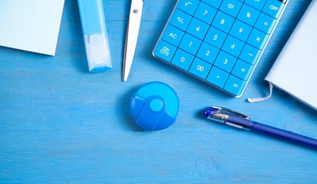 Kalkulator, notatka, gumka nożyczki, długopis, marker, karteczki na niebieskim tle.