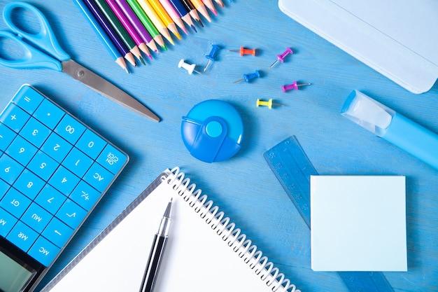 Kalkulator, ołówki, notatka, gumka nożyczki, długopis, marker, karteczki na niebieskiej powierzchni.