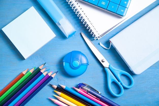 Kalkulator, ołówki, notatka, gumka nożyczki, marker, karteczki na niebieskiej powierzchni.