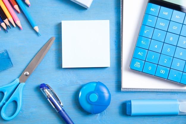 Kalkulator, ołówki, notatka, gumka nożyczki, marker, karteczki na niebieskim tle.