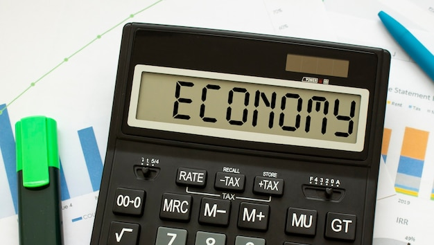 Kalkulator oznaczony gospodarka leży na dokumentach finansowych w biurze