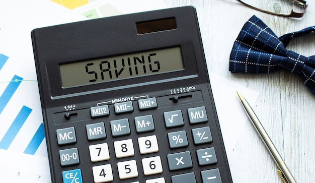 Kalkulator oznaczony oszczędność leży na dokumentach finansowych w biurze. pomysł na biznes.