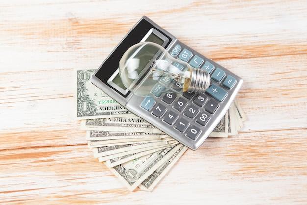 Kalkulator, pieniądze i żarówka na drewnianej scenie