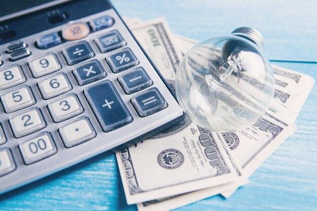 Kalkulator, pieniądze i żarówka na stole