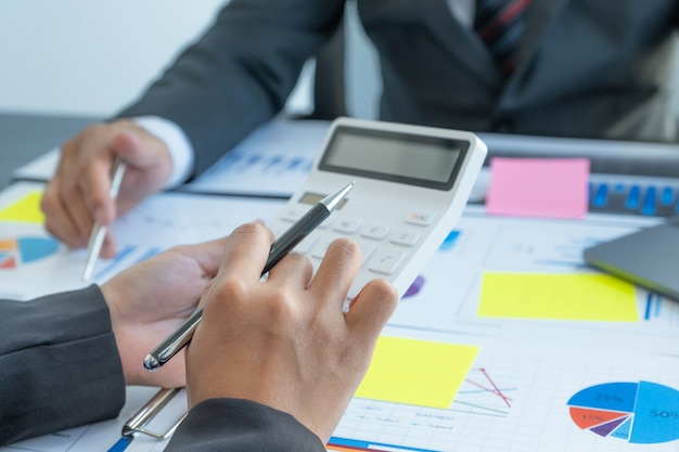 Kalkulator ręczny, spotkanie zespołu kobiet i biznesmenów w celu zaplanowania strategii zwiększania dochodów firmy