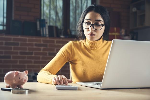 Kalkulator ręka kobieta z komputerem na stole