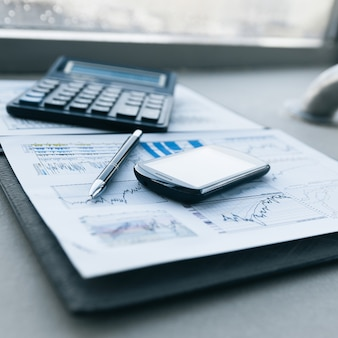 Kalkulator, smartfon i dokumenty finansowe dotyczące biznesu