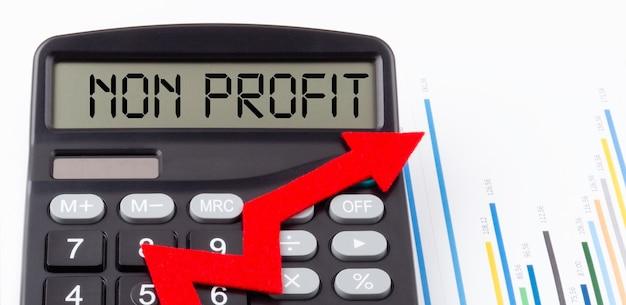 Kalkulator z czerwoną rosnącą strzałką i napisem non profit na wyświetlaczu