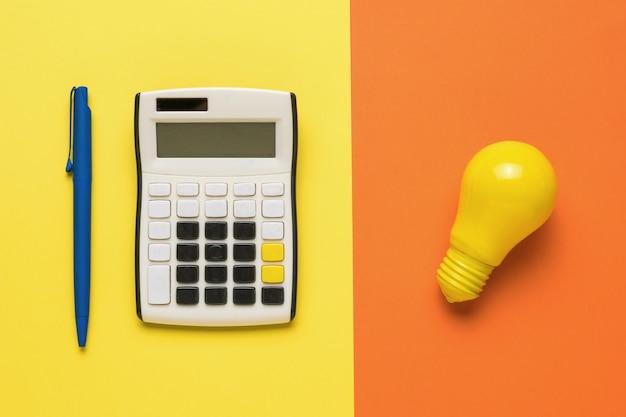 Kalkulator z długopisem i żarówką na pomarańczowym i żółtym tle.