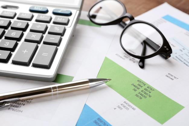 Kalkulator z dokumentami i okularami na stole. koncepcja podatkowa