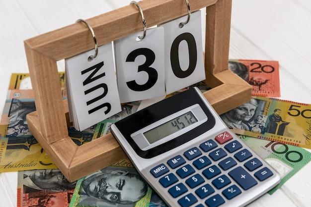 Kalkulator z drewnianym kalendarzem i banknotami dolara australijskiego