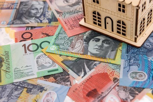 Kalkulator z drewnianym modelem domu w dolarach australijskich