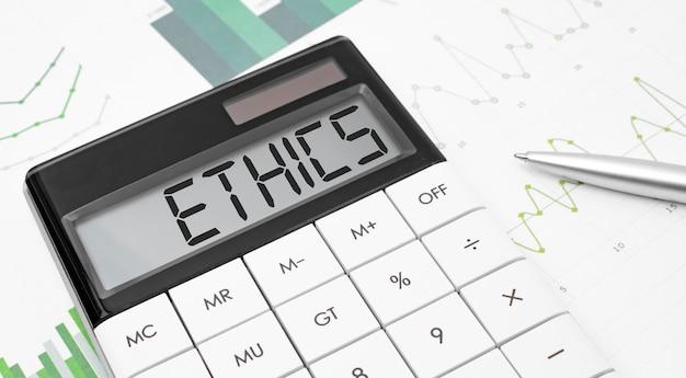 Kalkulator z napisem etyka na wyświetlaczu z wykresem i okularami