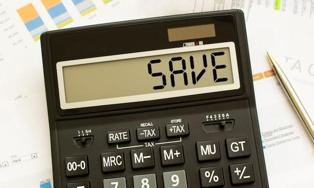 Kalkulator z napisem save leży na dokumentach finansowych w biurze