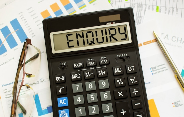 Kalkulator z napisem zapytanie leży na dokumentach finansowych w biurze. pomysł na biznes.