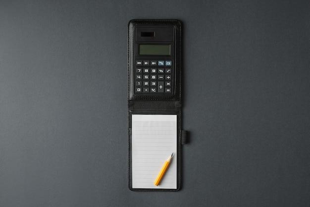 Kalkulator z notatnikiem i ołówkiem połączony na szarej ścianie w widoku poziomym z góry.