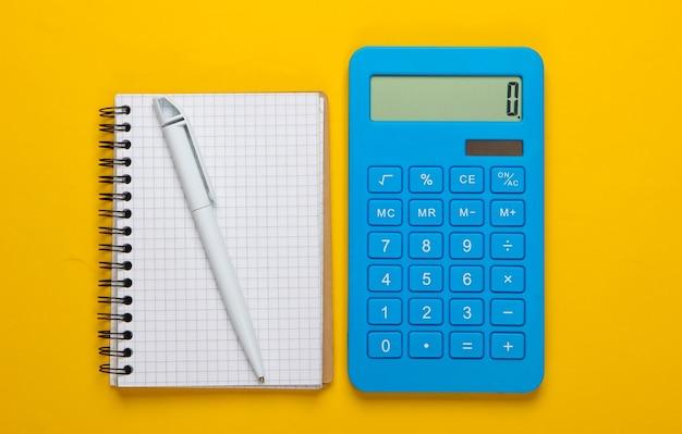 Kalkulator z notatnikiem na żółtym tle. proces edukacji. widok z góry. leżał na płasko