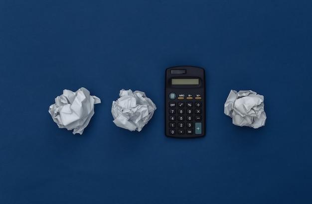 Kalkulator z zmiętymi papierowymi kulkami na klasycznym niebieskim tle. kolor 2020. widok z góry