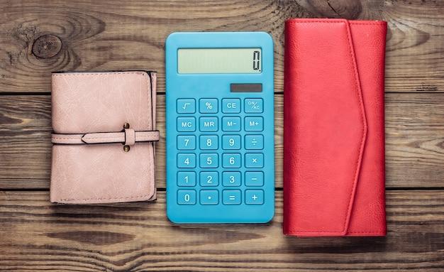 Kalkulator ze skórzanym portfelem na drewnianym stole
