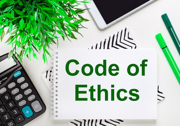 Kalkulator, zielona roślinka, telefon, marker, notes z napisem kodeks etyczny na pulpicie