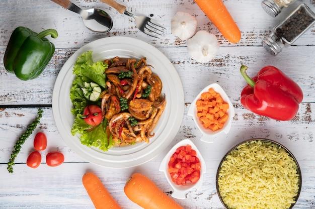Kalmary smażone z pastą curry na białym talerzu, z warzywami i dodatkami na białej drewnianej podłodze.