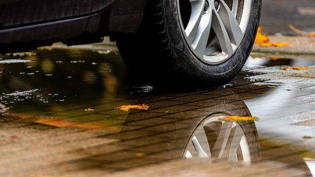 Kałuża na chodniku z odbiciem koła samochodu i kolorowymi jesiennymi liśćmi