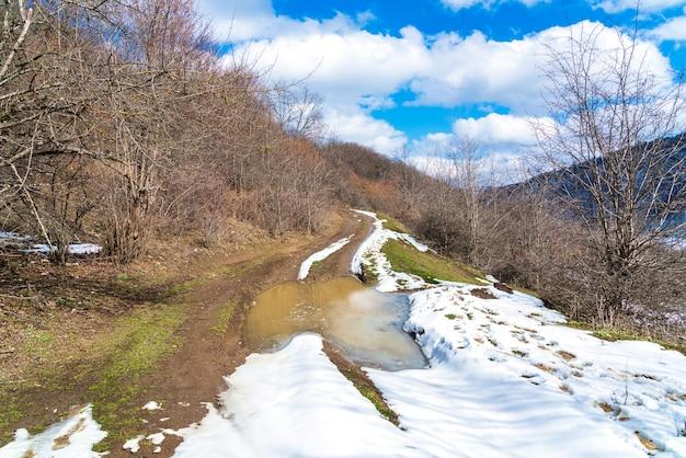 Kałuża na polnej drodze, topniejący śnieg, wiosna