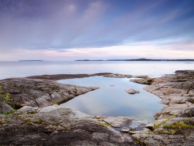 Kałuża spokojnej wody na skalistym brzegu. jezioro ładoga. republika karelii, rosja