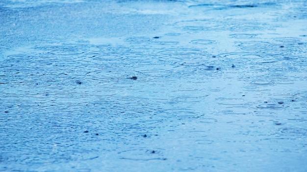 Kałuża z kroplami deszczu i kręgami na powierzchni wody w rzece, w tle deszcz kałużowy