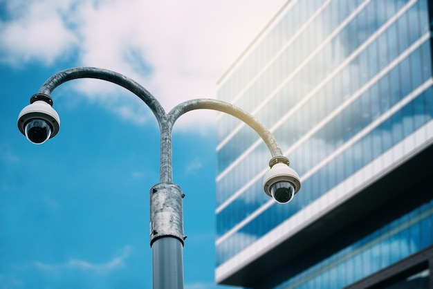 Kamera bezpieczeństwa z szklanym budynkiem na tle