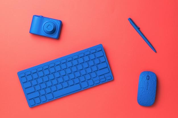 Kamera, bezprzewodowa klawiatura i mysz na czerwonej powierzchni. stylowe akcesoria dla biznesu i freelancerów. leżał na płasko.