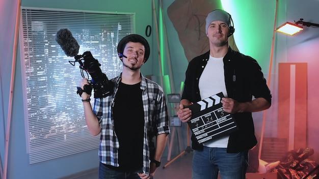 Kamera mężczyzna i asystent producenta uśmiecha się do kamery.