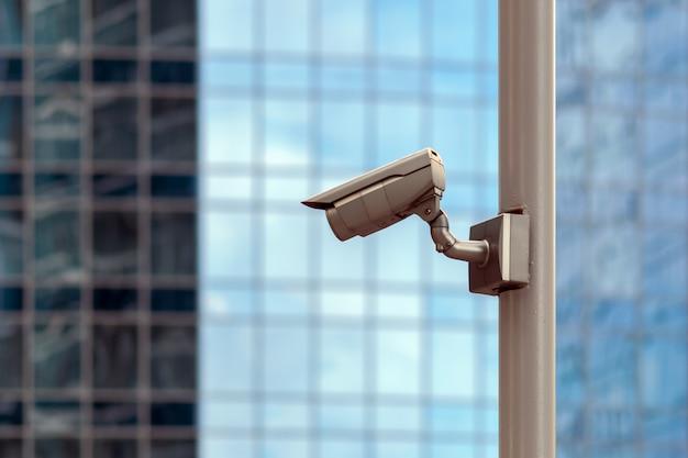 Kamera monitorująca na tle szklanej fasady budynku